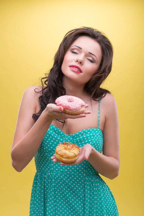 Woman with sweets. Half-length portrait of dark-haired woman wearing nice mint dotted dress holding two doughnuts and decided which one she wants to eat royalty free stock photos