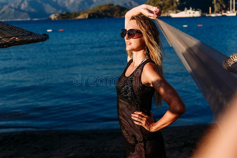 Sexy woman in a transparent tunic in the bright sunset light on the sea royalty free stock photos