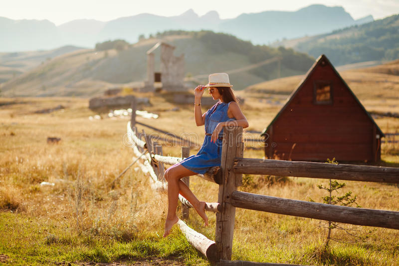 Woman travel countryside alone. Wooden houses and mountains background stock photography