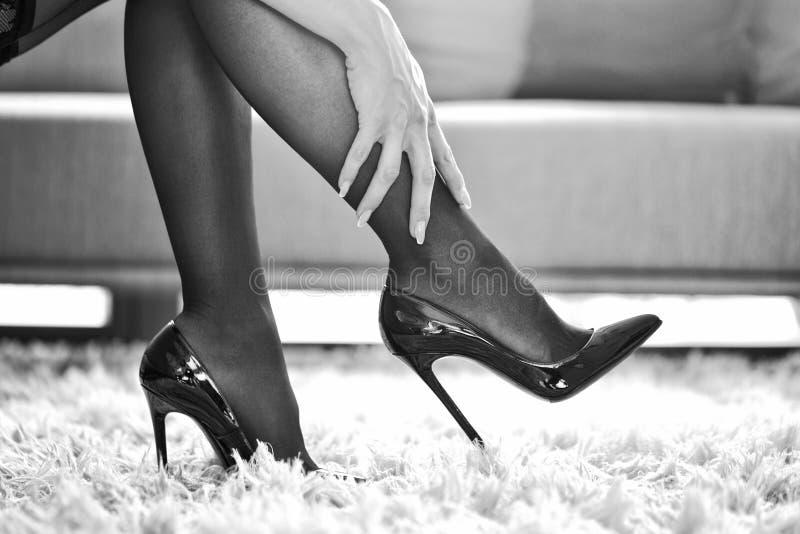 Woman in underwear touching legs closeup black and white. Woman in underwear touching legs indoor closeup, black and white stock photo