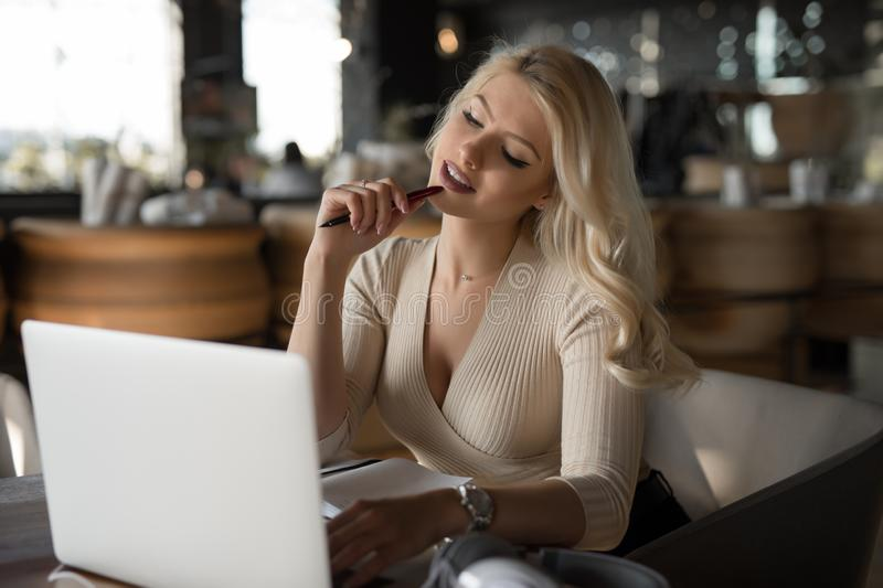 Sexy woman using laptop pc sitting in cafe royalty free stock image