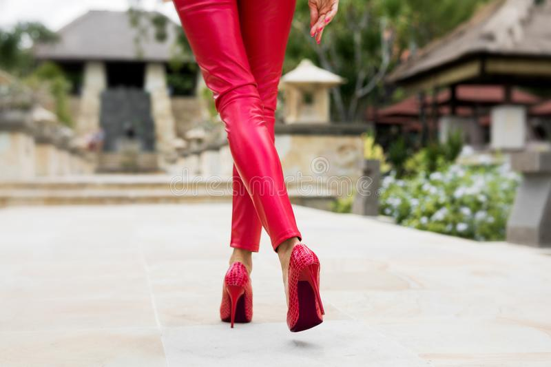 woman walking in red pants and red heels royalty free stock images