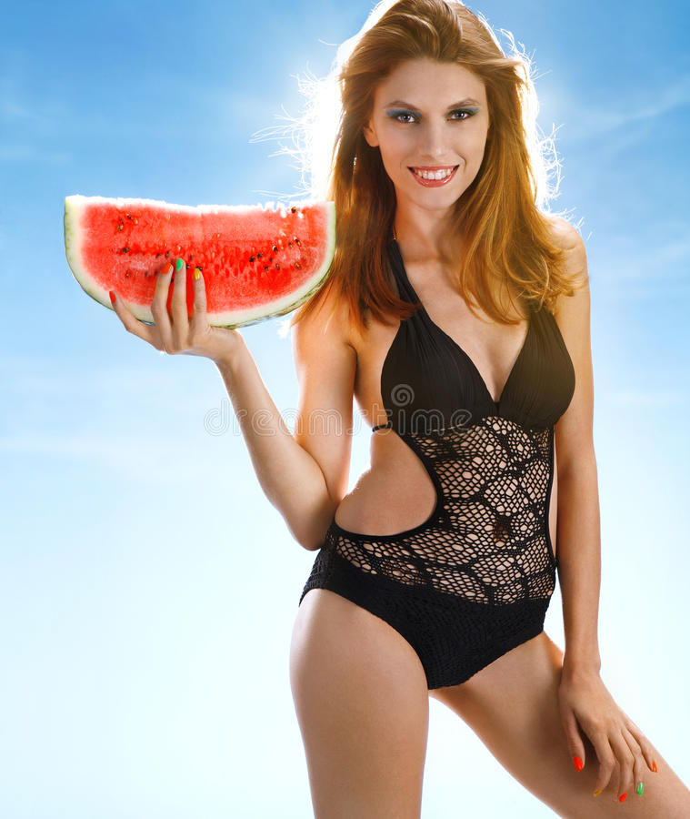 Woman with watermelon slice. Portrait of cheerful girl wearing swimsuit holding red ripe watermelon slice in her hand on blue background stock photos