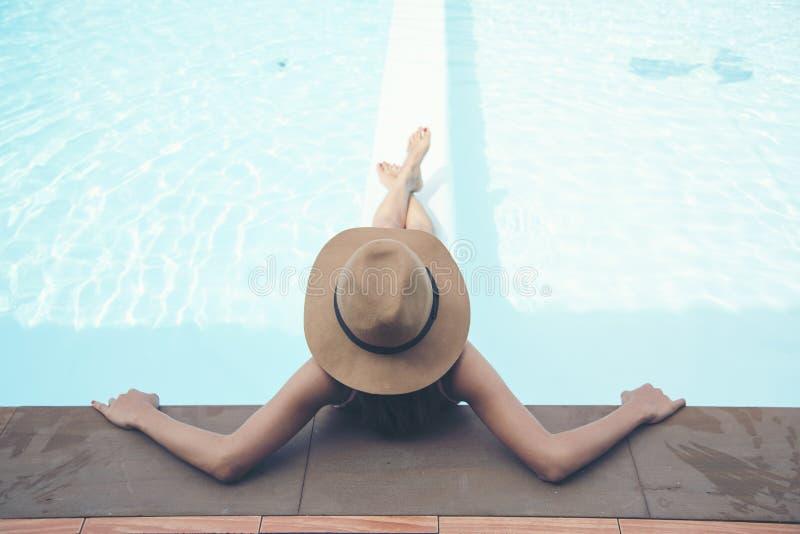 woman wear bikini and big hat relaxing in the pool royalty free stock photo