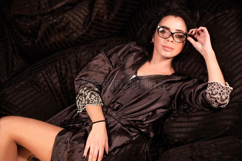 Woman wearing robe and glasses posing for camera. Woman wearing robe and glasses posing for camera stock photography
