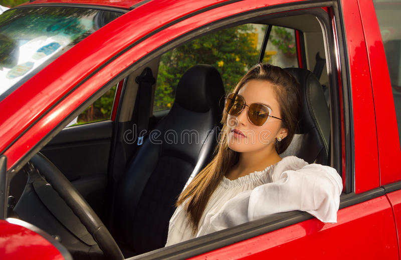 Woman wearing sunglasses and posing for camera while her arm is over the window of her red car.  stock photo