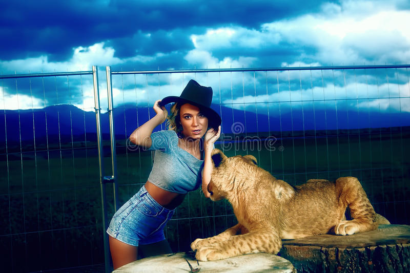 woman in a western hat with lion cub on stock photos