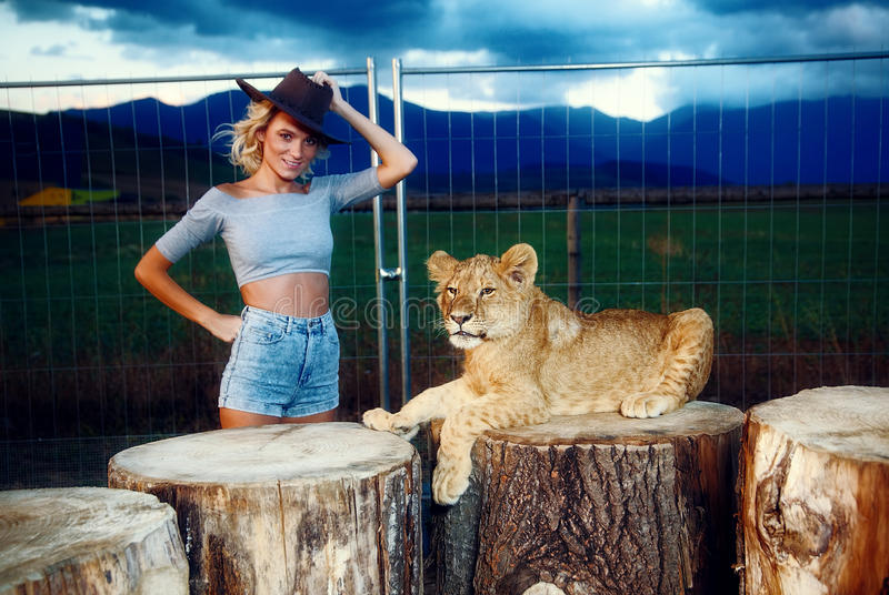 woman in a western hat with lion cub on royalty free stock photos