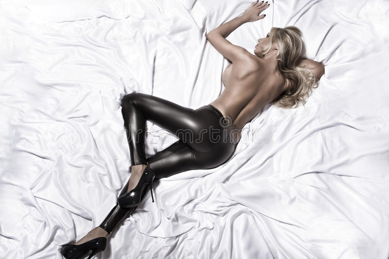 Woman on the white bed. Blonde glamour woman on the white bed royalty free stock image