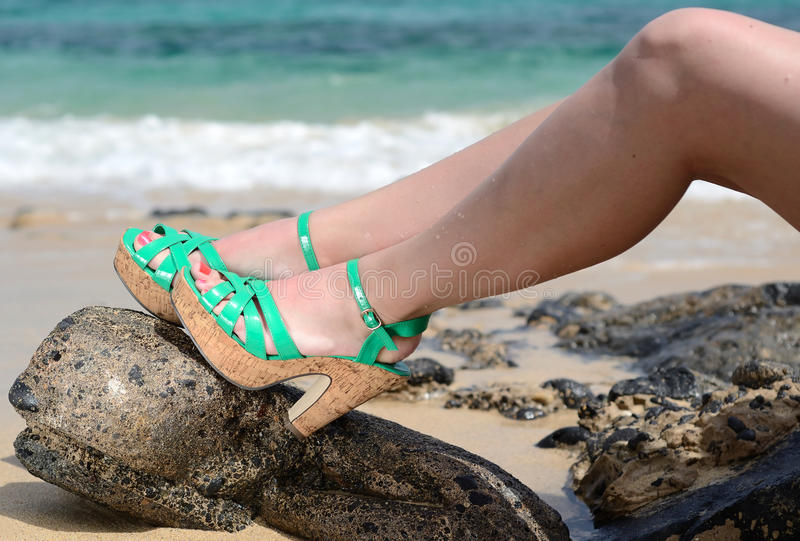 Women on the beach. Women's heels on tropical beach royalty free stock images