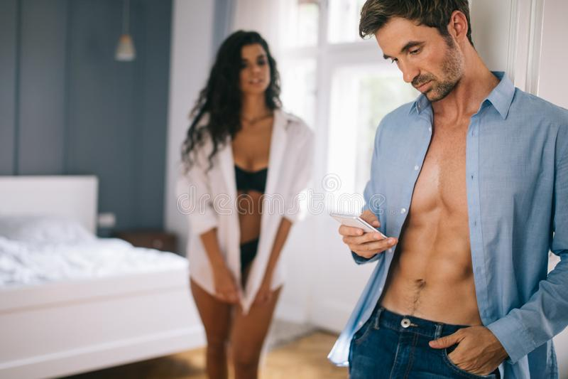 Woman noticing her husband checking his smartphone and texting his lover. Women noticing her husband checking his smartphone and texting his lover stock image