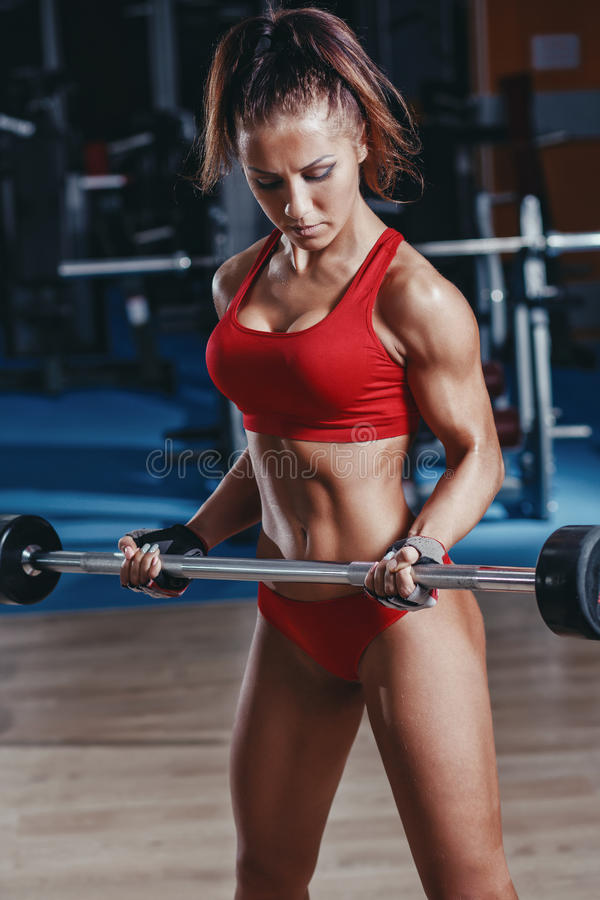young athletics girl doing biceps barbell curl exercises in gym royalty free stock photos