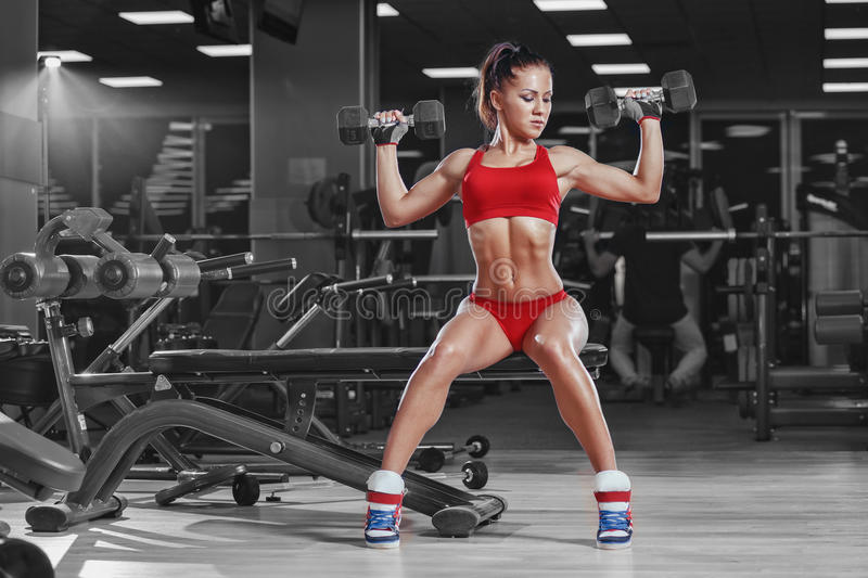 Young athletics girl doing dumbbells press exercises sitting on bench in gym. Young athletics girl doing dumbbells press exercises. Fitness muscled woman in red stock photography