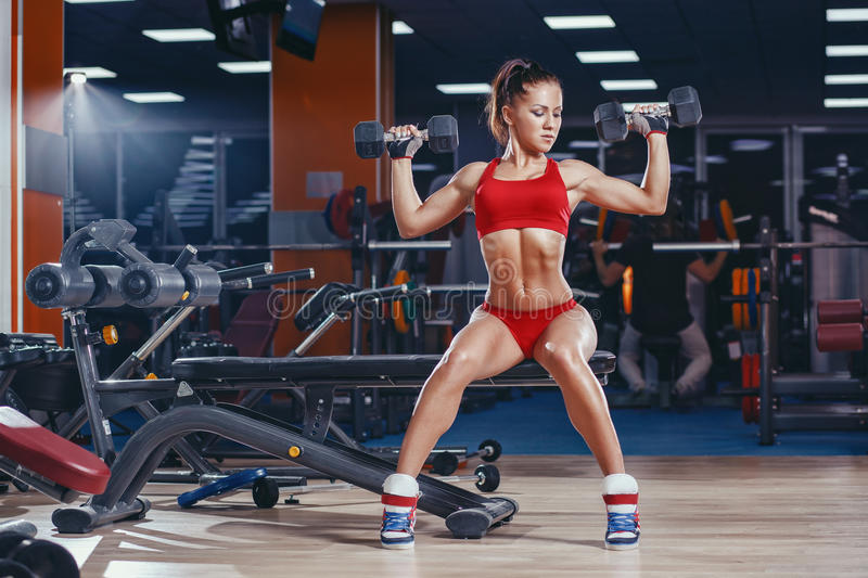 young athletics girl doing dumbbells press exercises sitting on bench in gym stock photo