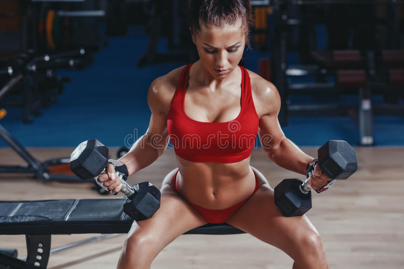 young athletics girl with perfect slim fit with dumbbells in gym stock photos