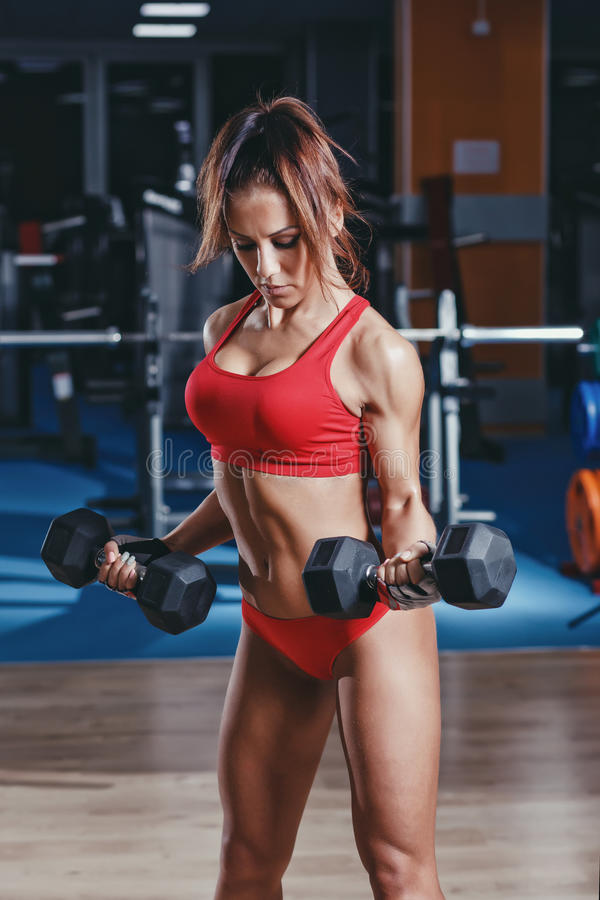 Young athletics girl posing with barbell on her shoulders. Fitness muscled woman in red sport clothing in gym resting after exercises stock photos