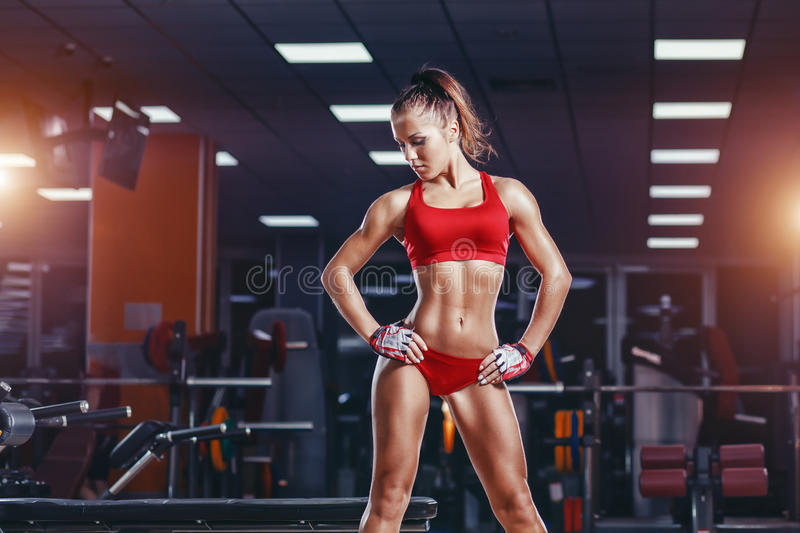 young athletics girl resting after fitness training exercises in gym stock image