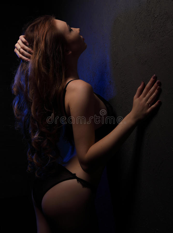 young beautiful woman with curls in sensual black lingerie, lighted with blue in studio near wall, shoulder and hair in l royalty free stock photos
