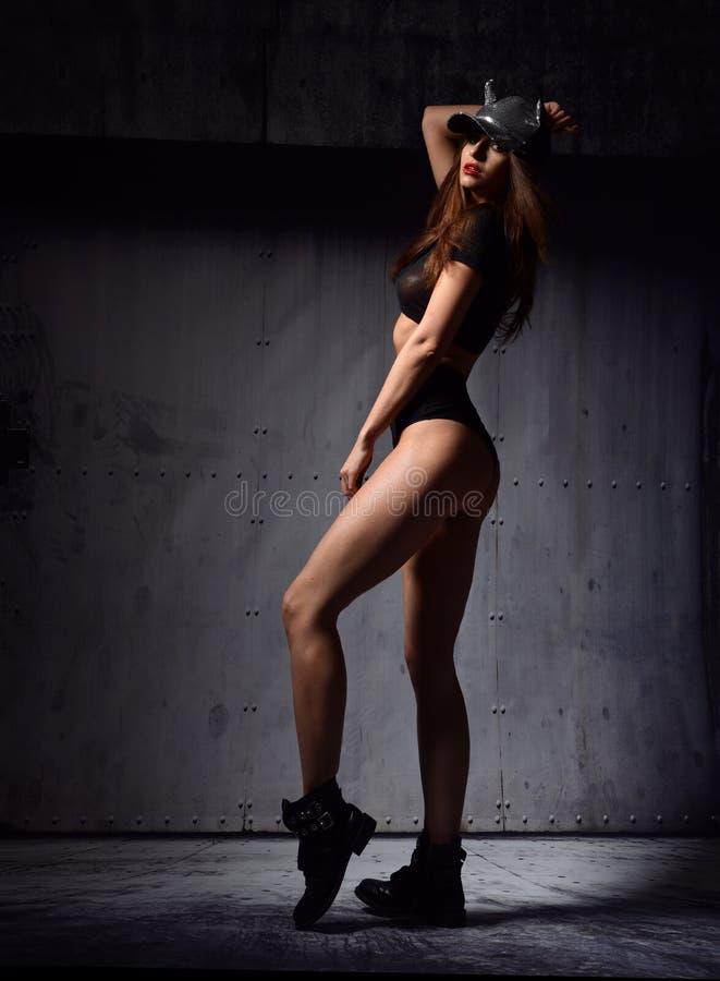 Young beautiful woman posing in black modern bikini vest an. D cap on dark grey garage door background royalty free stock photo