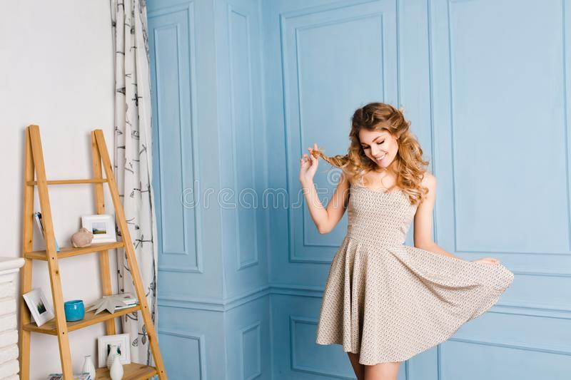 young blond girl with curly hair closing her eyes and playing with her dress and hair. She wears short dress royalty free stock photography