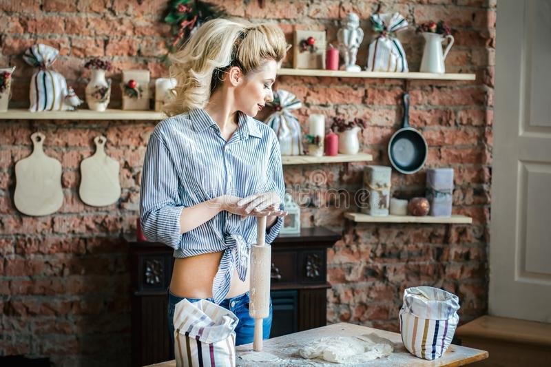 Young woman blonde erotic prepares dough in the kitchen. housewife with bags of flour and with rolling pin in the kitchen. Young blonde woman erotic prepares royalty free stock photography