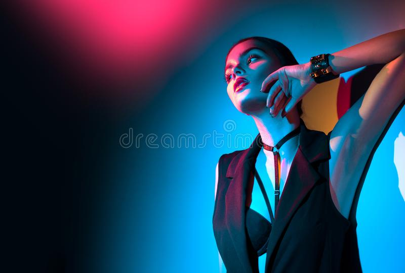 Young brunette girl in black clothes, fashion accessories posing in studio. Over colorful background royalty free stock image