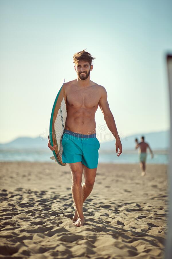 Sexy young caucasian beardy male walking on the sunny beach, holding surfboard, smiling royalty free stock image