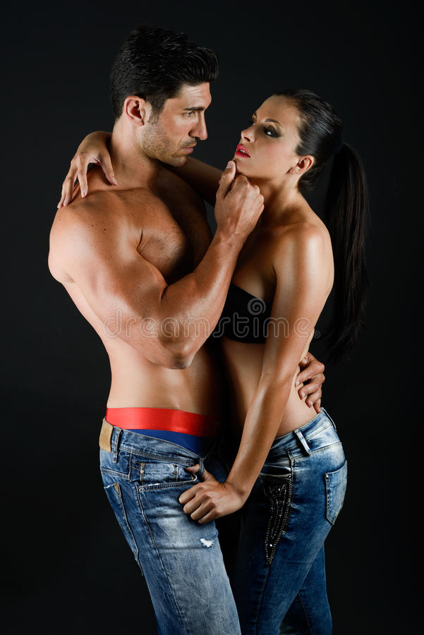 Young couple with blue jeans standing together. Studio shot royalty free stock images
