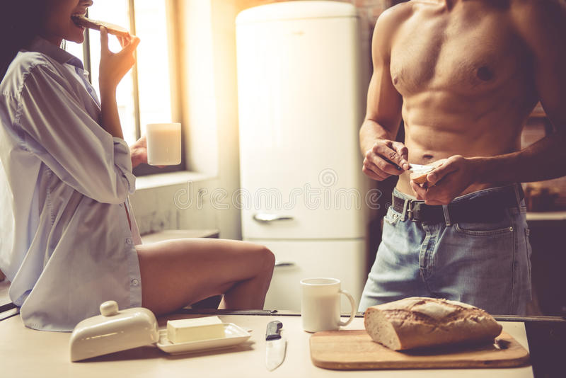 young couple in kitchen stock images