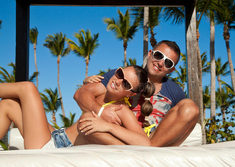 Download Young Couple Relaxing Near Pool On A Beach Bed Stock Photo - Image of cool, indulgence: 39500458