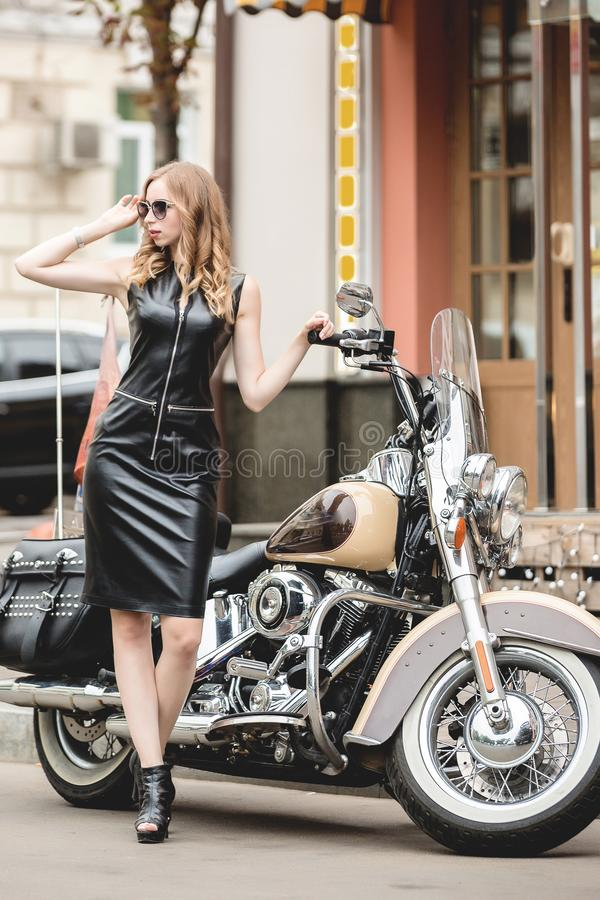 Sexy young elegance woman near old fashioned custom motorcycle. Outdoor lifestyle portrait. Sexy young woman near old fashioned custom motorcycle. Outdoor stock images