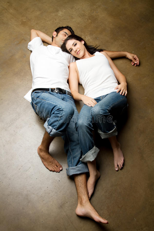 young ethnic couple relaxing on the floor royalty free stock images