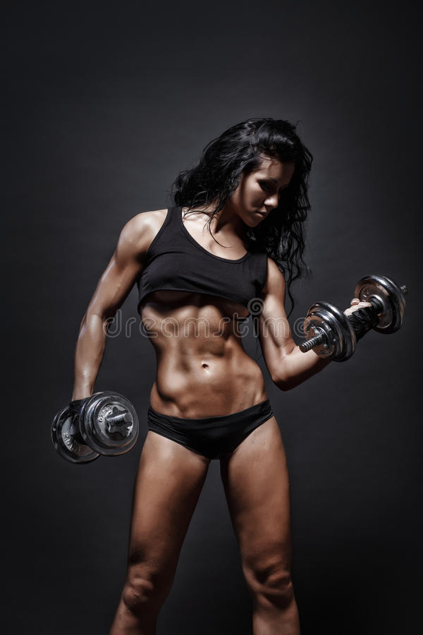 Young fitness girl doing workout with dumbbells over black background. Fitness woman in sport wear with perfect fitness body workout royalty free stock photography