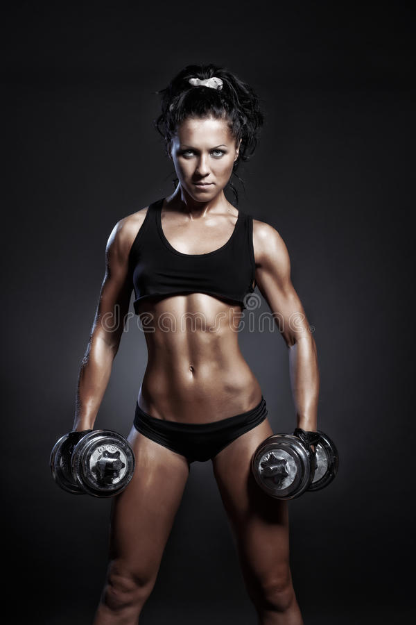 Young fitness girl doing workout with dumbbells over black background. Fitness woman in sport wear with perfect fitness body workout stock image