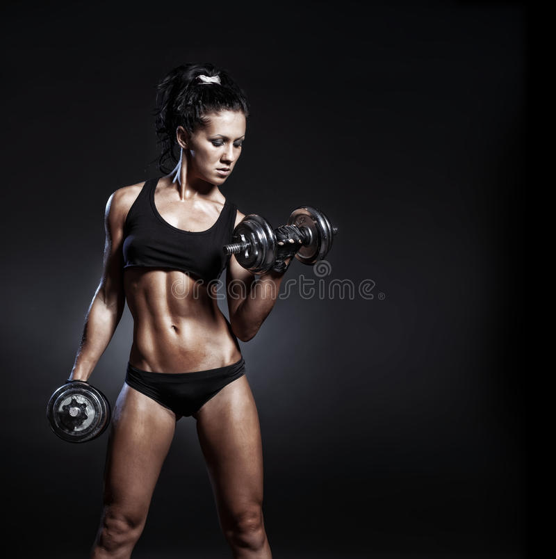 Young fitness girl doing workout with dumbbells over black background. Fitness woman in sport wear with perfect fitness body workout stock photos