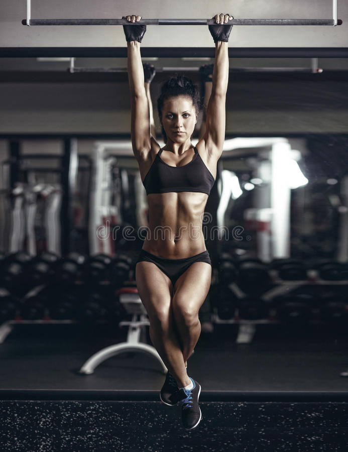 young fitness girl pulls up in the gym. stock photos