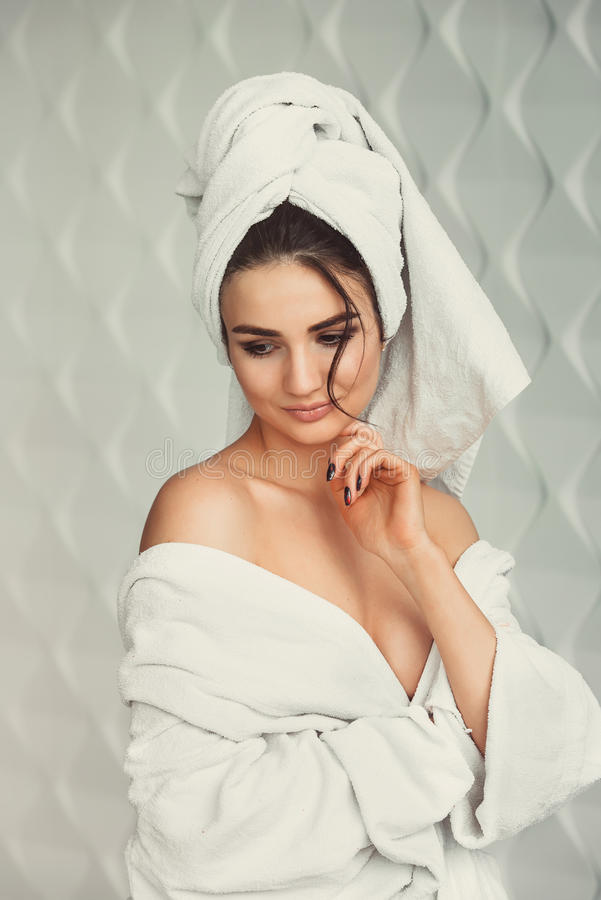 young girl with dark hair, big eyes and dark eyebrows wearing white bath robe whith towel on her head. stock images
