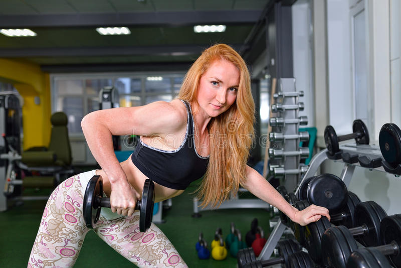 young girl exercises with dumbbells. Fitness woman workout in gym stock photos