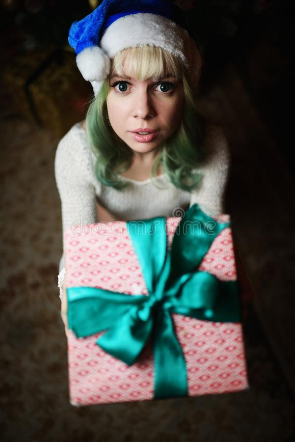 young girl gives gift under Christmas tree stock image