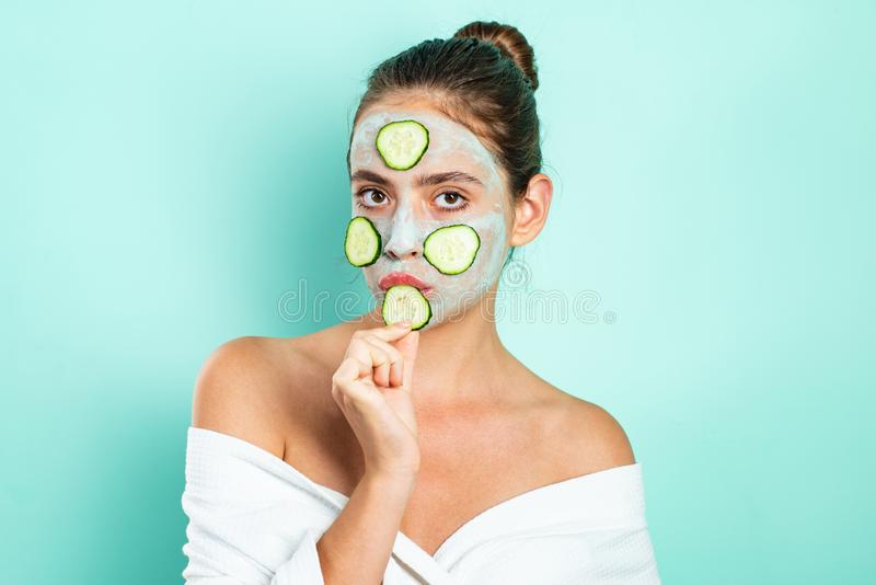 Sexy young girl with a mask for skin and slices of cucumbers on face. Happy mood and selfcare. Natural beauty concept royalty free stock photo