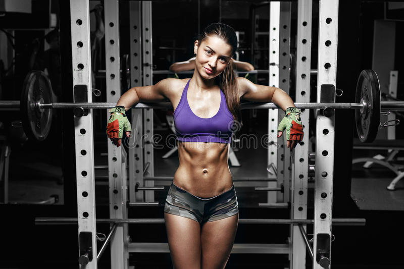 Young girl with perfect abs resting after squat exercises. Fitness brunette fit woman leans on barbell royalty free stock image