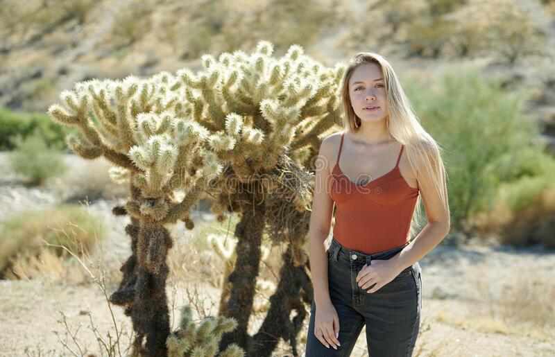 Stunning young Latina woman poses in front of cholla cactus. Sexy young Latina woman posing in desert wearing rust colored tank top and blue jeans - cactus royalty free stock image