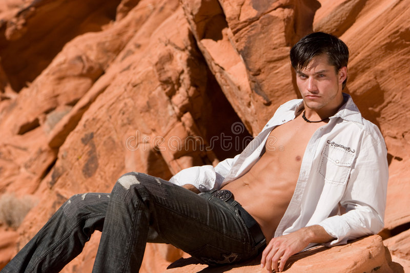 Young man. On red rocks stock image