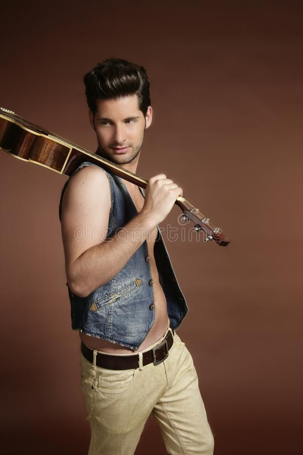 Young man musician guitar player on brown. Handsome young man musician guitar player portrait on brown royalty free stock photo