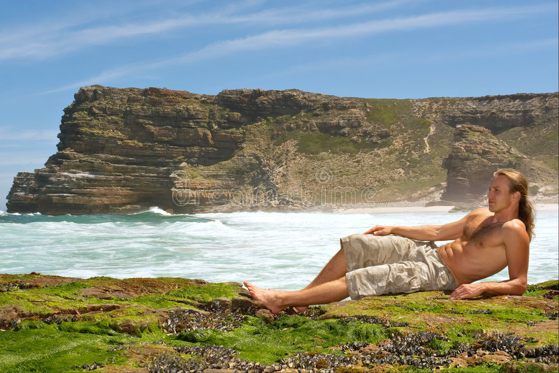 Young man relaxing on rocks. Sea-misty mountain background. Shot in the Cape of Good Hope and Cape Point Nature Reserve, Table Mountain National Park, near royalty free stock image