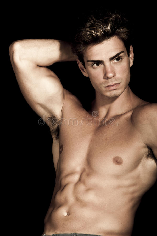 Young man shirtless. Gym muscular body. A young italian man is posing shirtless. He has a hand behind his head. Muscular body, hes a well-defined royalty free stock photos