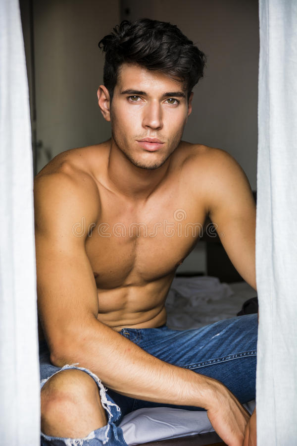 young man sitting shirtless by curtains stock photos