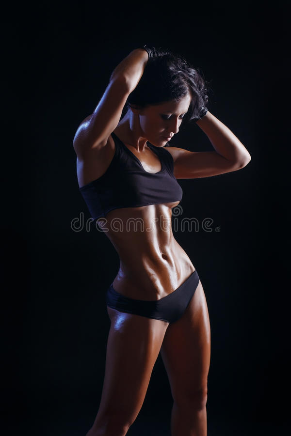 Young muscled fitness brunette girl posing over black background. Fitness woman in sport wear with perfect fitness body royalty free stock image