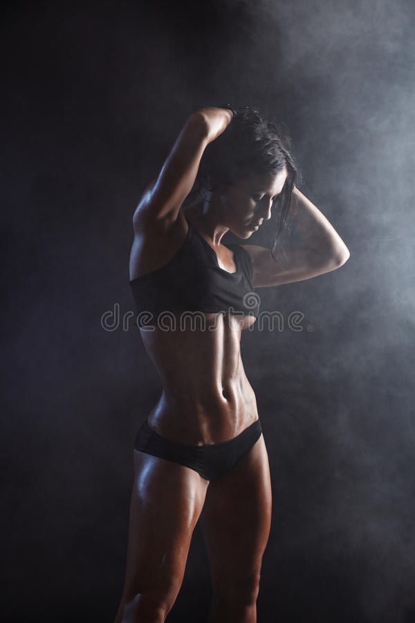 Young muscled fitness brunette girl posing over black background. Fitness woman in sport wear with perfect fitness body stock images