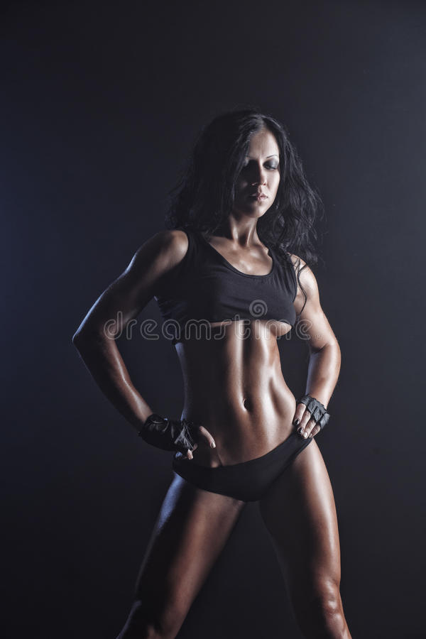 Young muscled fitness brunette girl posing over black background. Fitness woman in sport wear with perfect fitness body stock photography